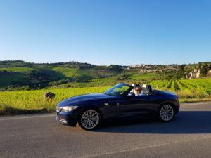 Dirigindo em conversível BMW com capota aberta pela Toscana